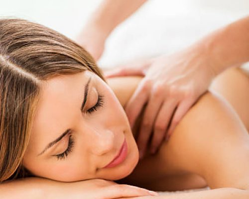 Woman relaxing at spa with her eyes closed and receiving back massage.